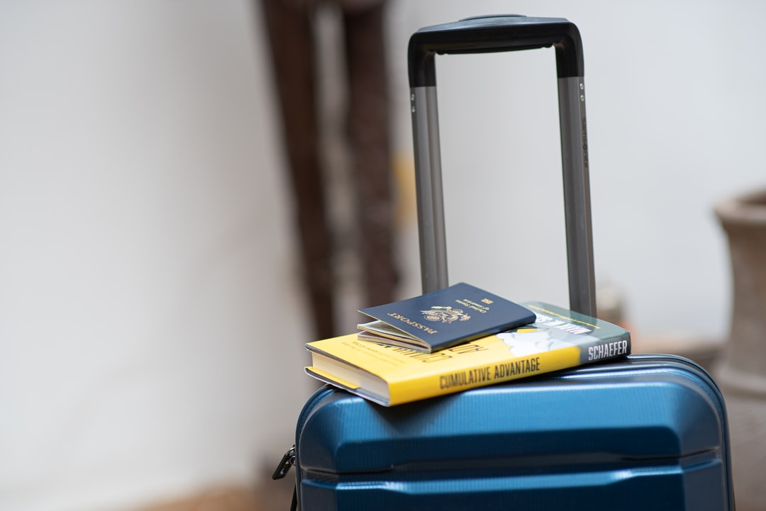 A laptop computer sitting on top of a suitcase
