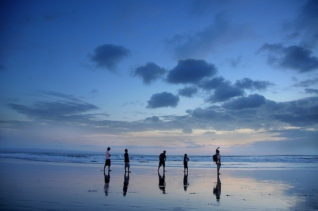A group of people walking on a beach