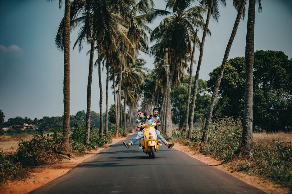 A person riding a motorcycle down a street next to a palm tree